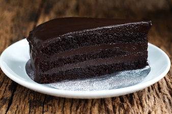 Piece of dessert chocolate cake on white plate.