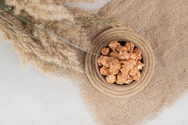 Кусок ткани, подставка для посуды, миска попкорна со вкусом карамели и стебли иглграсса на мраморном столе.