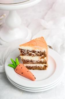 Кусок праздничного кремового торта с мастикой из моркови, стопка белых блюдца, белый фон, вертикальный формат.