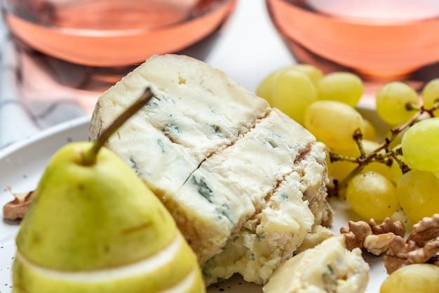 Кусок французского винограда голубого сыра, меда и груши на десерт, фон рецепта еды. крупным планом,