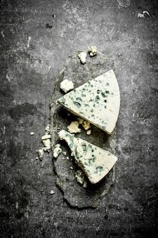 프랑스 블루 치즈 조각. 돌 테이블에.