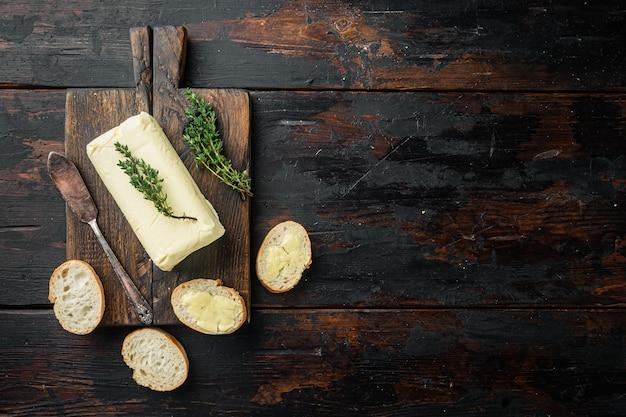 오래 된 어두운 나무 테이블에 신선한 버터 조각