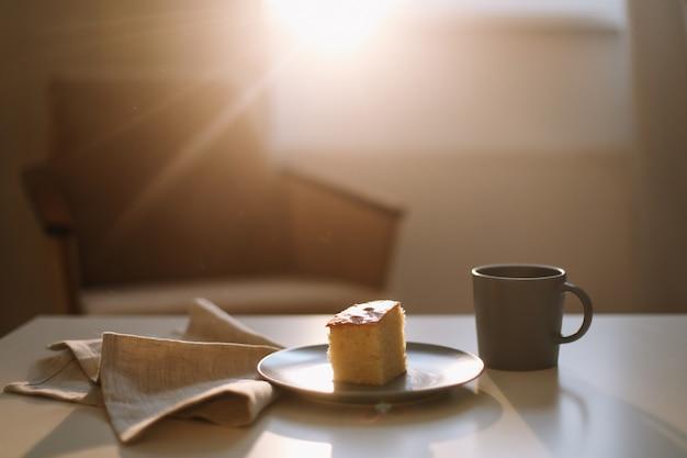 Кусок свежего домашнего торта с чашкой капучино на столе