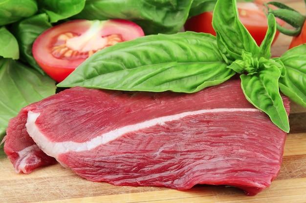 Кусок свежего мяса из базилик и помидор на деревянной доске