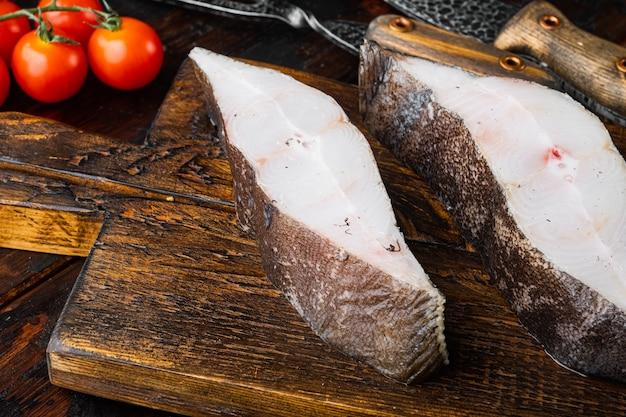 古い暗い木製のテーブルの背景に、食材とローズマリーのハーブと新鮮な生のオヒョウの魚のセットの一部