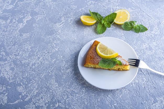 Кусок свежеиспеченного лимонного пирога, торта или торта из манной крупы на тарелке, подается с дольками лимона и мятой