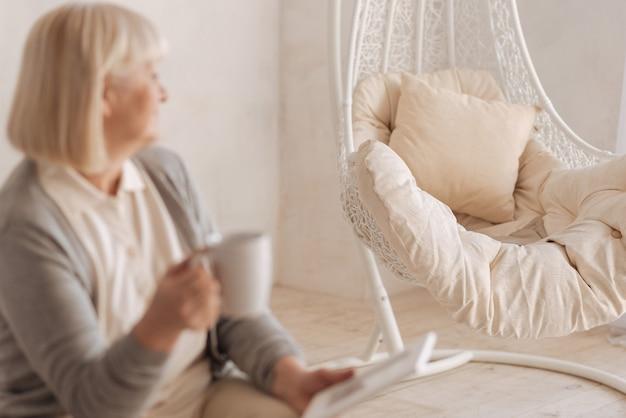 Предмет мебели. селективный фокус пустого кресла, стоящего в комнате, когда на него смотрит милая пожилая женщина