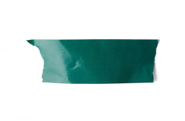 Кусок зеленой бумаги липкой лентой на белом фоне