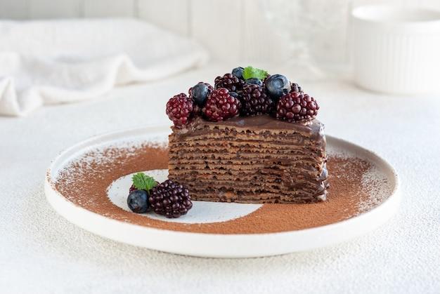 白い皿にベリーで飾られた自家製チョコレートクレープケーキ