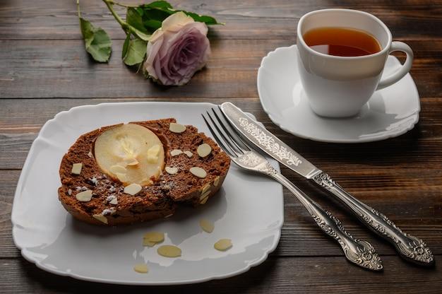 하얀 접시에 생강과 카 다몬으로 만든 초콜릿 배 컵 케이크의 조각