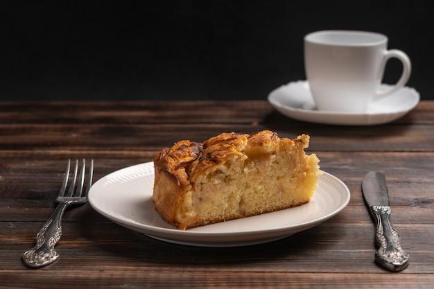 Кусок домашнего традиционного яблочного пирога из корниша на белой тарелке на деревянном столе выборочный фокус