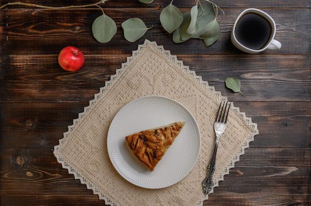Кусок домашнего традиционного яблочного пирога корниш на белой тарелке с вилкой на салфетке. чашка чая, яблоко и ветка с листьями