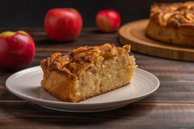 Кусок домашнего традиционного яблочного пирога с кукурузой на белой тарелке