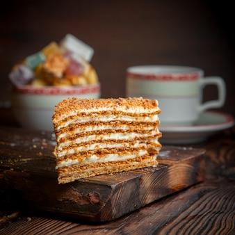 Кусок медового торта с сахаром и чашкой чая на доске с продуктами