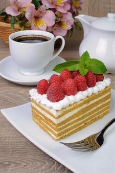 휘핑크림과 라즈베리를 곁들인 꿀 케이크 조각