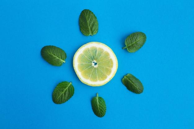 青い表面にレモンとミントの葉の作品。太陽の創造的なイメージ。平面図。ダイエットの最小限のコンセプト。