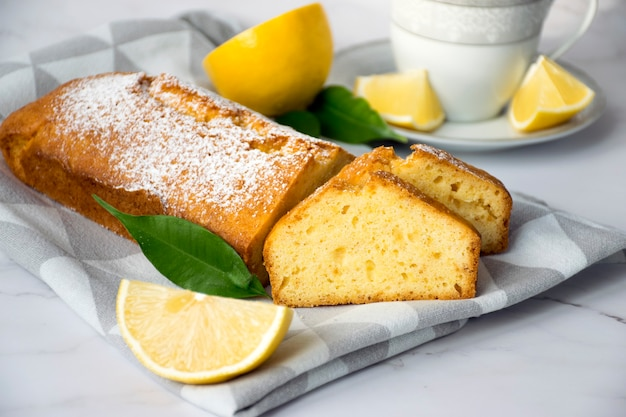 Кусок лимонного торта на кухонном полотенце с лимонами и чашкой чая. легкий рецепт цитрусового десерта для повседневного приготовления.