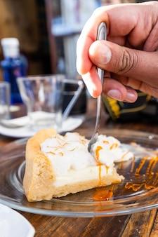 포크로 남성의 손에 의해 절단되는 레몬 파이 조각 수평