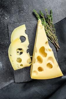 Кусок сыра маасдам с большими отверстиями. черный фон. вид сверху