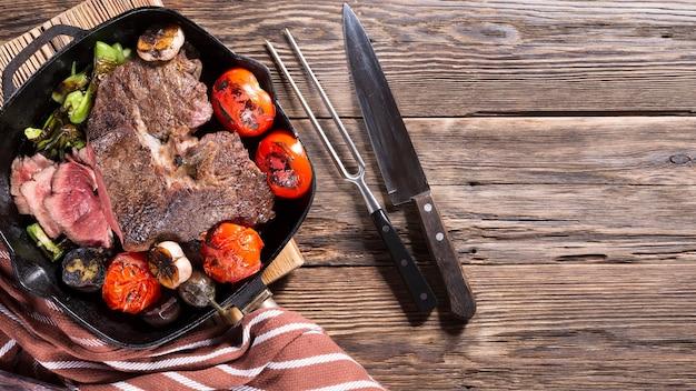 Кусок мяса средней прожарки на сковороде-гриль с овощами, американская еда, крупный план сверху