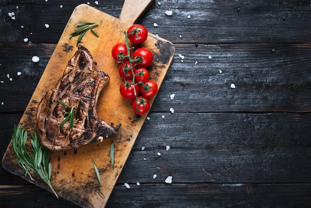 Кусок стейка средней прожарки, свежие овощи на столе, спелые помидоры. вкусный ужин для всей семьи.