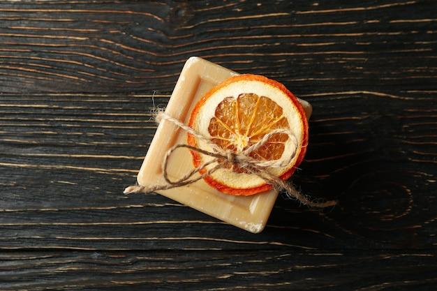 Кусок натурального оранжевого мыла на деревянных фоне