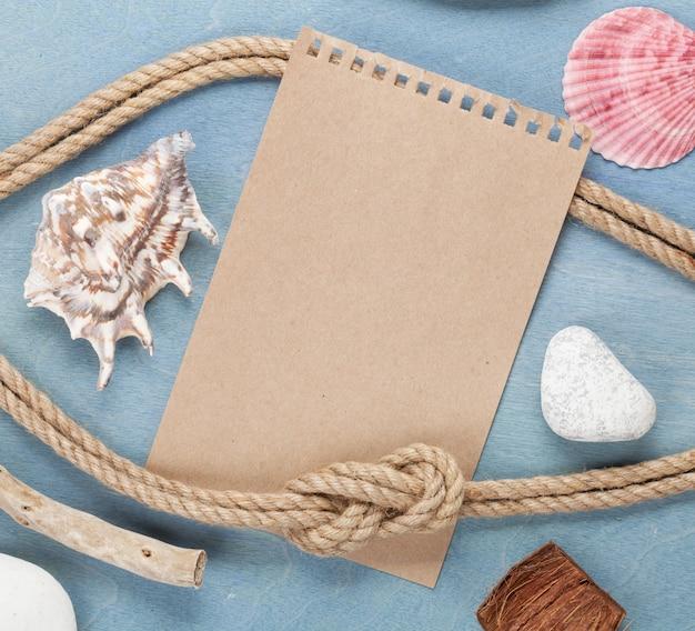 木製の背景に一枚の紙と海のもの