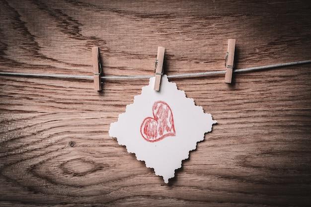 Кусок бумаги с сердцем, нарисованным на прищепке. фото с копией пространства