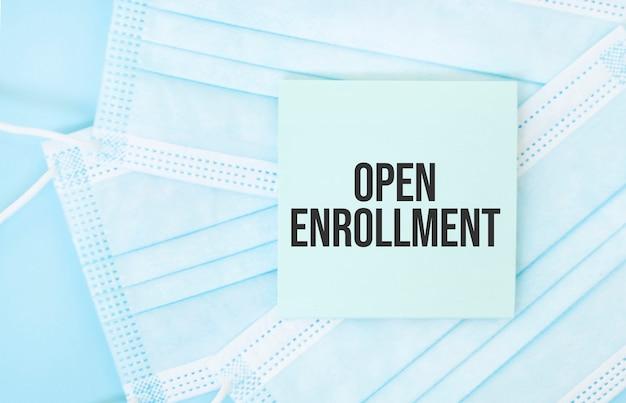 青い医療用マスクの山に「openenrollment」というフレーズが書かれた一枚の紙
