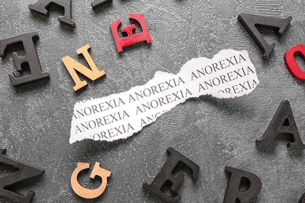 Кусок бумаги с текстом анорексия на серой поверхности