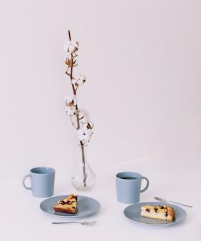 Кусок пирога на тарелке с чашкой чая на завтрак белый стол