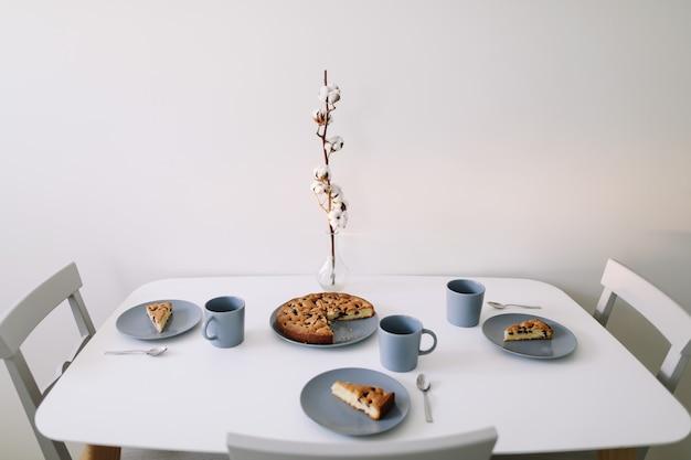 Кусок пирога на тарелке с чашкой чая на белом столе