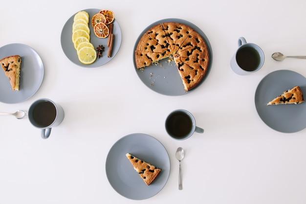 Кусок пирога на тарелке с чашкой чая на белом столе Premium Фотографии