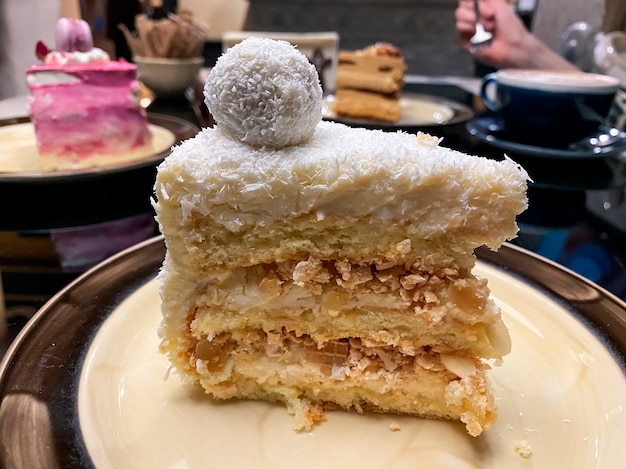 Кусок розового торта с бисквитом, розовым кремом и украшением поверх торта в виде макарон и сушеной розы на тарелке в ресторане.