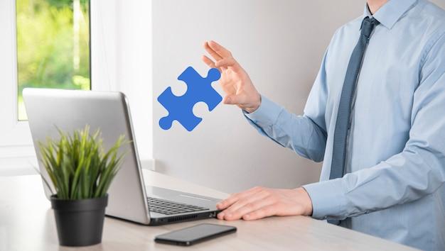 Кусок головоломки в его руках. концепция сотрудничества, совместной работы, помощи и поддержки в бизнесе