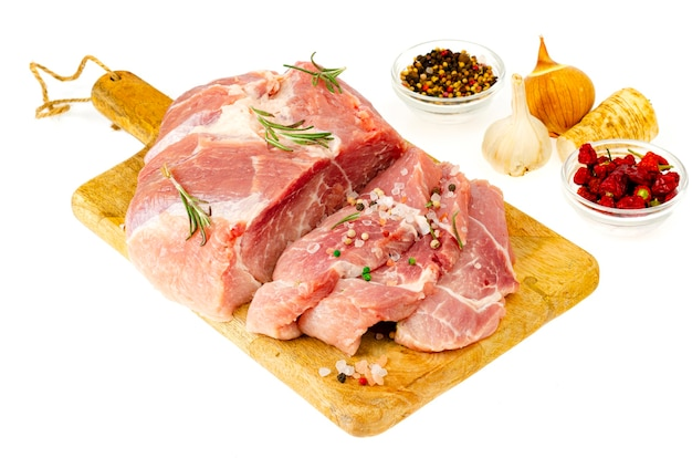 Кусок сырой свежей свинины со специями для приготовления мясных блюд. студийное фото