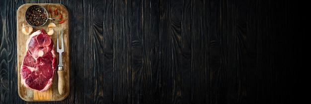 暗い木製のテーブルにスパイスと生の子羊の肉の一部、コピースペースの上面図