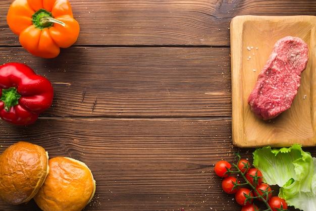 Кусок сырого мяса в приправах и свежих овощах на деревянном столе, вид сверху, никто. сырой стейк, перец и зелень