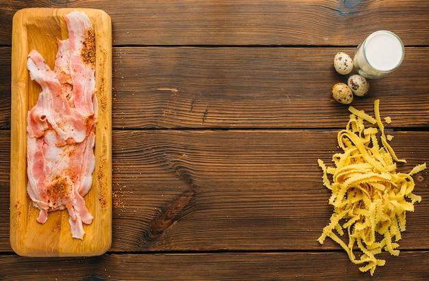 Кусок сырого мяса в приправе, макаронах и яйцах на деревянном столе, вид сверху