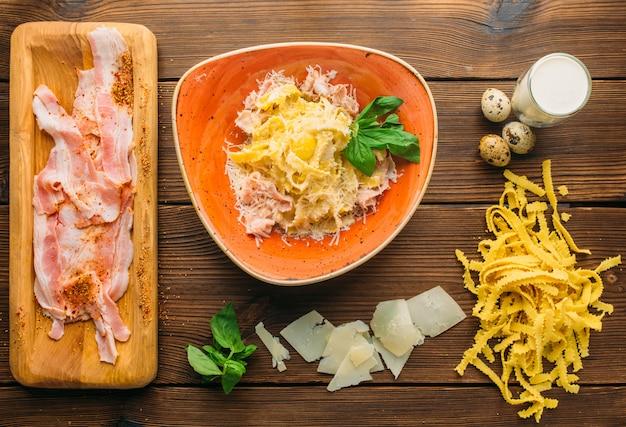 Кусок сырого мяса в приправе, пасте, сыре, травах и яйцах на деревянном столе, вид сверху