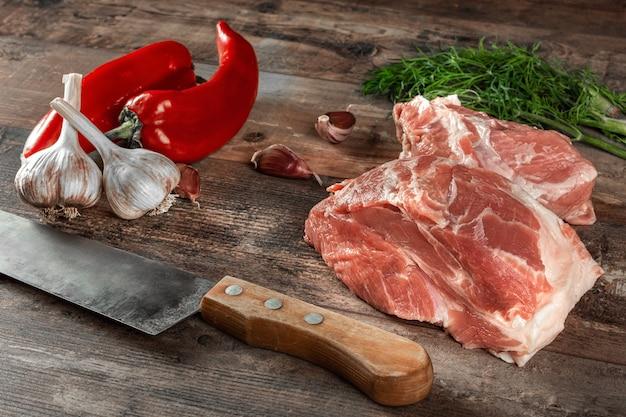 Готовый к приготовлению кусок сырого мяса с зеленью и специями