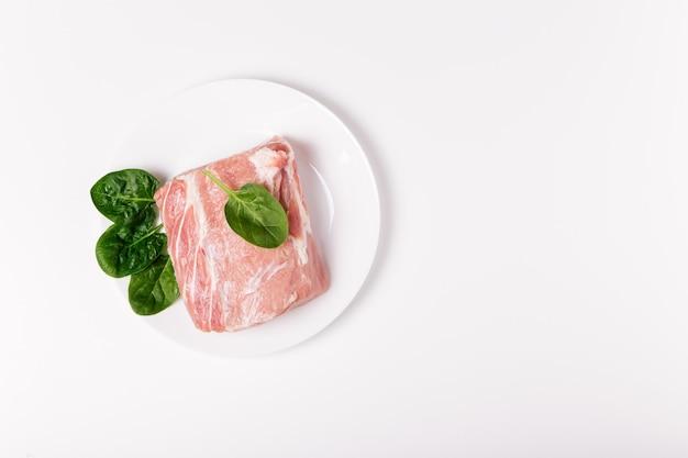 화이트 세라믹 접시에 시금치와 원시 돼지 고기의 조각. 흰색 바탕에 고기 전체 조각입니다. 평면 위치, 평면도, 복사 공간