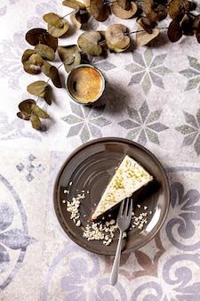 プレート上の生のビーガンチーズケーキの一部。華やかなセラミックテーブルの上のブラックコーヒーとユーカリの枝のカップ。日光。フラットレイ