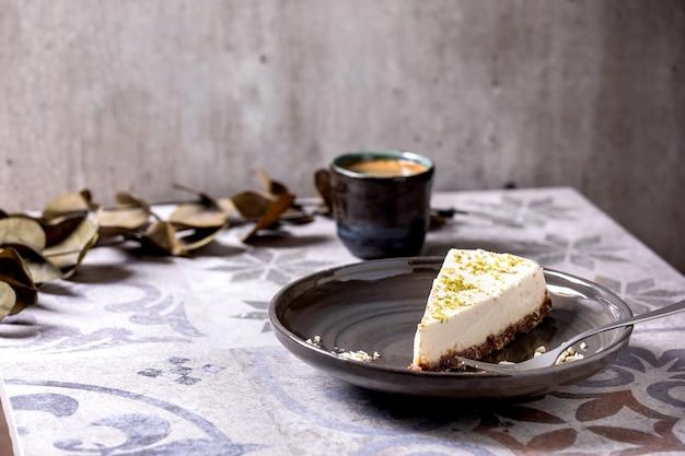 プレート上の生のビーガンチーズケーキの一部。華やかなセラミックテーブルの上のブラックコーヒーとユーカリの枝のカップ。日光