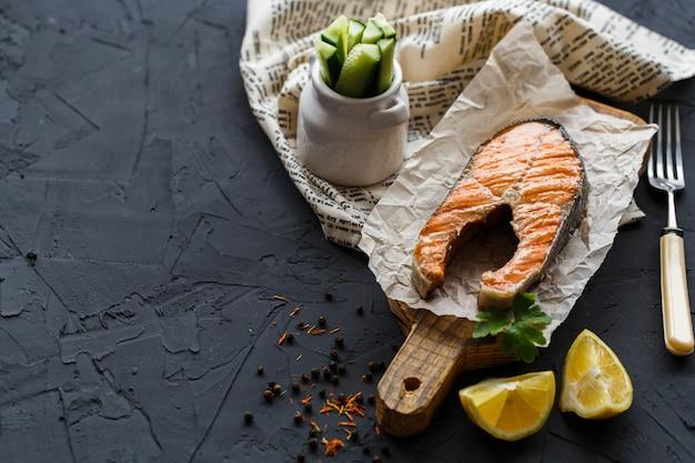 Кусок красной рыбы, запеченный на деревянной доске и текстильной салфетке, с лимоном, зеленью и огурцами