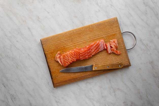 Кусок малосольного лосося, нарезанный дольками на кухонной доске