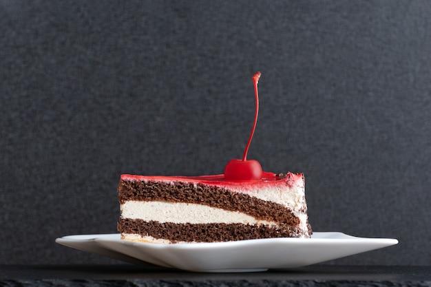 Кусок бисквитного торта, украшенный вишней на белой тарелке. черный фон.