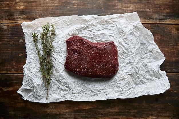 Кусок мяса стейка на крафт-бумаге с видом сверху ромеро
