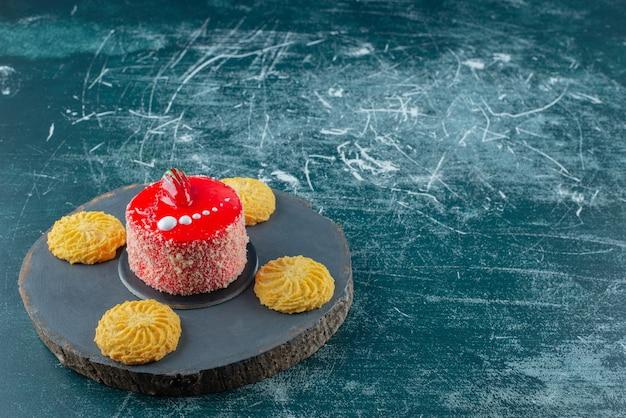 나무 조각에 비스킷과 함께 딸기 케이크의 조각.