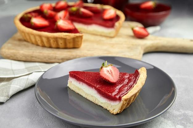 Кусок клубничного пирога со свежими ягодами на серой тарелке на сером каменном фоне
